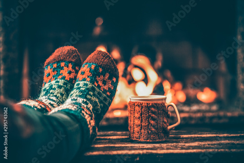 Photo Feet in woollen socks by the Christmas fireplace
