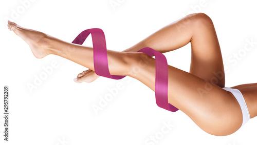 Fotografie, Obraz Women's legs with pink ribbon. Physical rehabilitation concept.