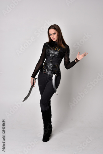 full length portrait of a pretty brunette woman wearing black leather fantasy costume Fototapete