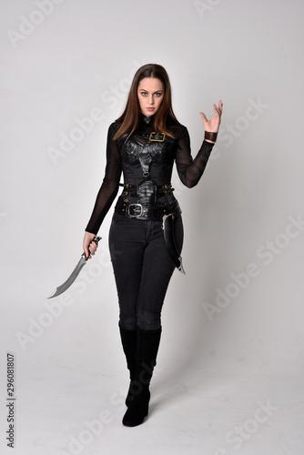 Billede på lærred full length portrait of a pretty brunette woman wearing black leather fantasy costume