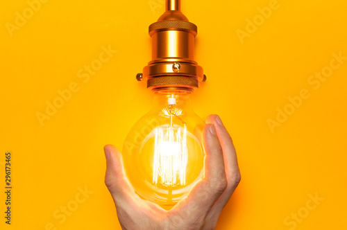 Vintage fashionable edison lamp in male hands on bright yellow background Fototapet