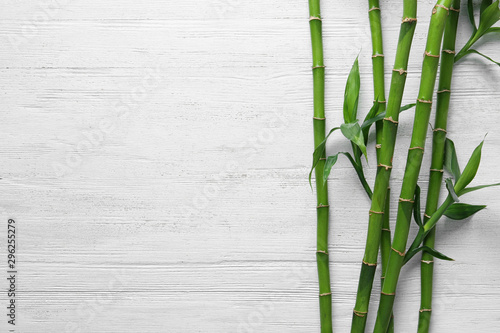 Green bamboo stems on white wooden background, top view Fototapeta