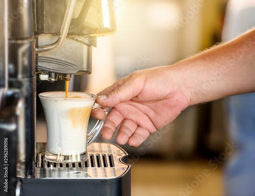 Hand taking coffee cup in automated coffee making machine. Fototapeta