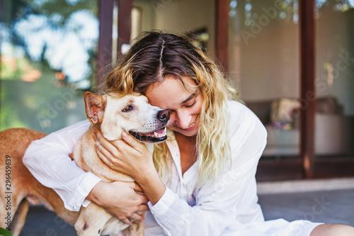 Canvas Print Beautiful caucasian woman hugging her mongrel dog pet