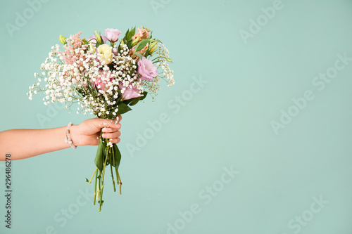 Obraz na plátne Female hand with bouquet of beautiful flowers on color background