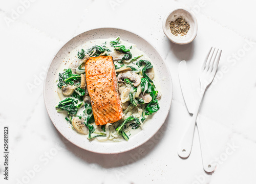 Stampa su Tela Roasted salmon with creamy spinach mushrooms sauce on a light background, top view