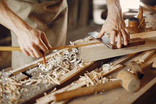 Fotografering Man working with a wood. Carpenter in a white shirt