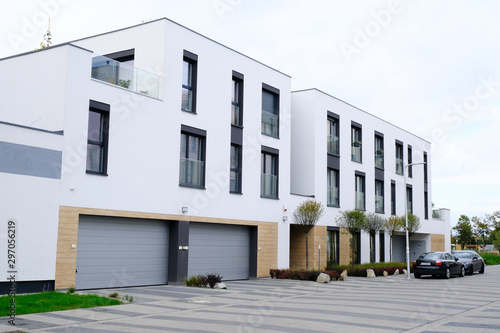 Fotografie, Obraz Modern white building with two garages and cars on a street.