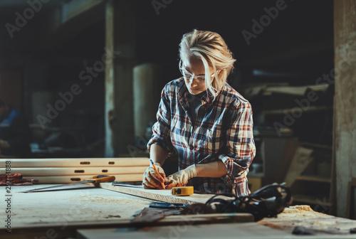 Billede på lærred Attractive middle aged woman carpenter designer works with ruler, make notches on the tree in workshop
