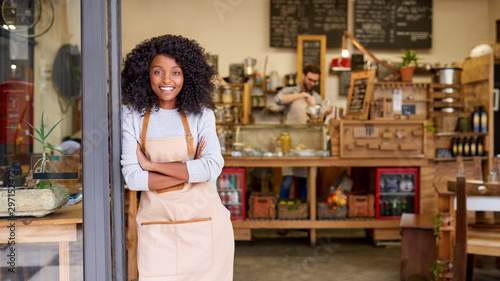 Valokuva Smiling African American barista standing welcomingly at a cafe door