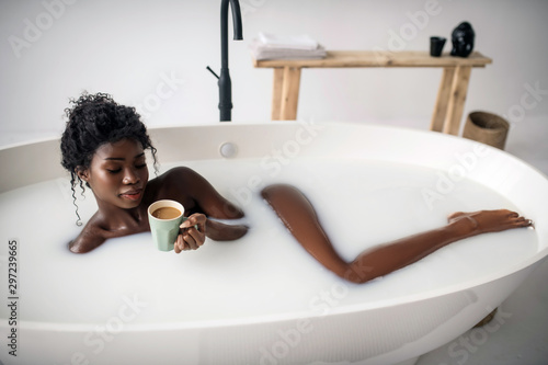 Curly woman chilling in bath and drinking coffee with milk Fototapeta
