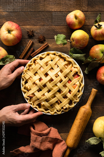 Fototapeta Homemade apple pie with pastry lattice on a rustic wooden table background