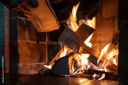 Hands put firewood in a kindled fireplace on a cold winter day Fototapeta
