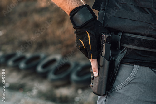Pulling out a gun from the holster on belt, close-up. Fototapeta