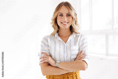 Fotografia Image of attractive elegant blonde woman standing in white office
