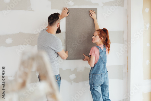 Young couple trying out new wallpaper at home