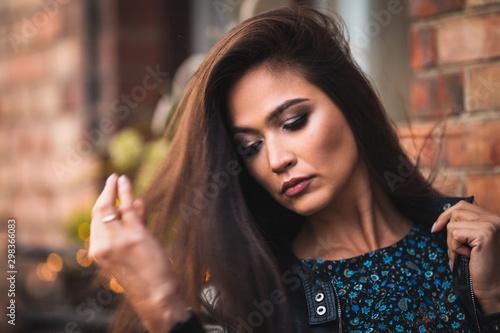 Attractive seductive sexy brunette straightens her thick long hair Fototapeta