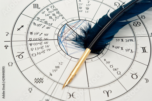 Foto quill pen in form ob blue feather lying on horoscope and zodiac signs like astro