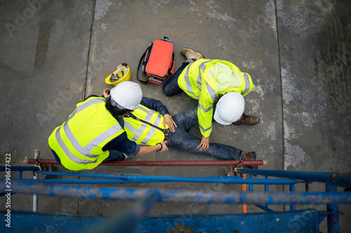 Obraz na płótnie Basic first aid training for support accident in site work, Builder accident fall scaffolding to the floor, Safety team help employee accident
