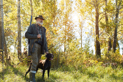 Valokuva Senior hunter and his dog in forest, look for prey, hunting on wild animals