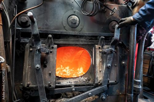 Fototapeta An open door to the furnace of a steam engine