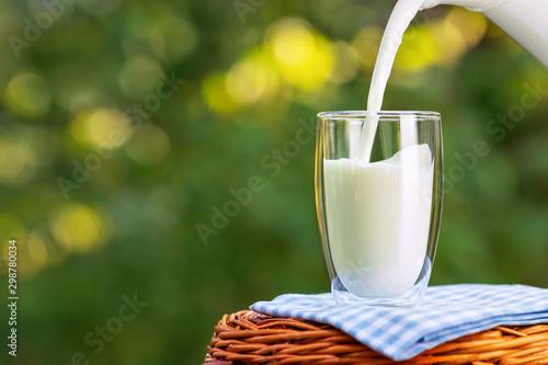 Fotografia milk from jug pouring into glass