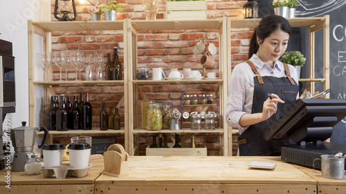 Photographie waitress girl in apron using finger touching screen of POS terminal in coffee shop