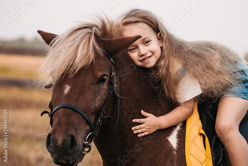 Carta da parati Adorable little girl riding a pony at summer