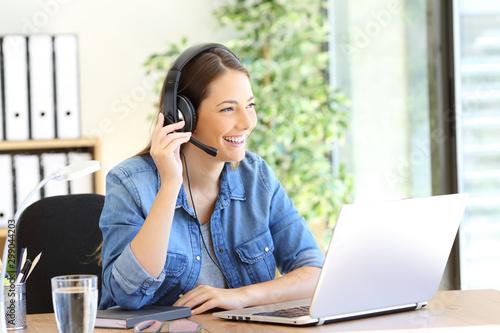 Happy tele operator attending call looking away Fototapeta
