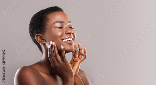 Stampa su Tela Happy afro woman touching soft smooth skin on her face