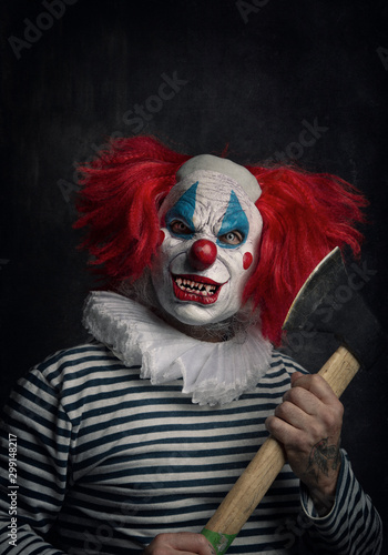 Cuadros en Lienzo Close-up of a scary evil clown with red hair, white eyes, bloody teeth, ax in hand and a menacing look