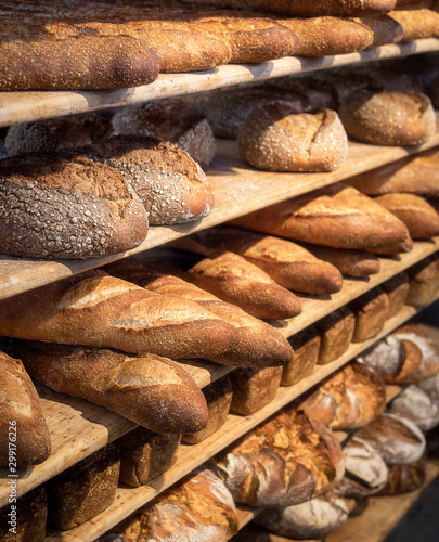 Fotografia Round breads and long french loaves on shelves. Baked goods.