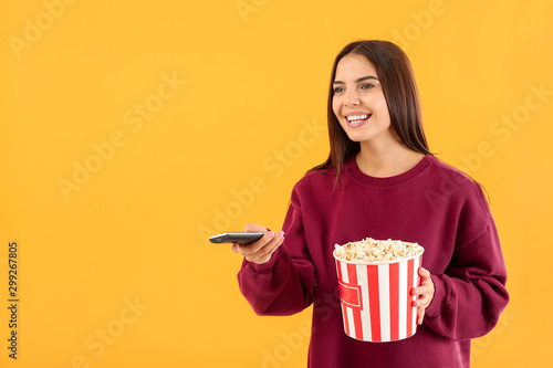 Young woman with popcorn and remote control on color background