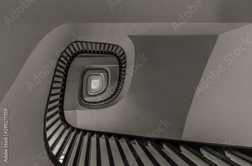 Gray scale low angle shot of a stairway going up surrounded by white walls