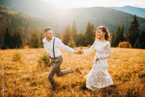 Leinwand Poster Sunset illuminates mountain hill where wedding couple walks