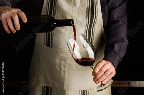 Hombre vertiendo vino tinto en copa de vino Fototapete