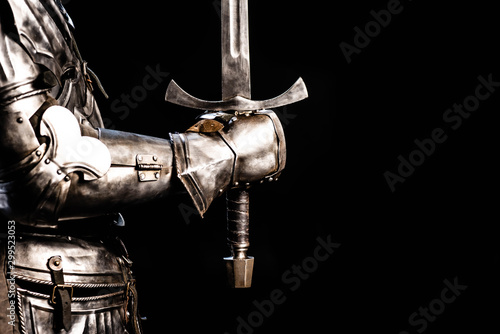 Fototapeta cropped view of knight in armor holding sword isolated on black