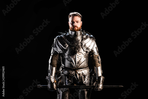 handsome knight in armor holding sword isolated on black Fototapete
