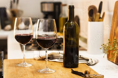 Fotografia Copas con vino tinto y botella sobre tabla de madera rústica en la cocina