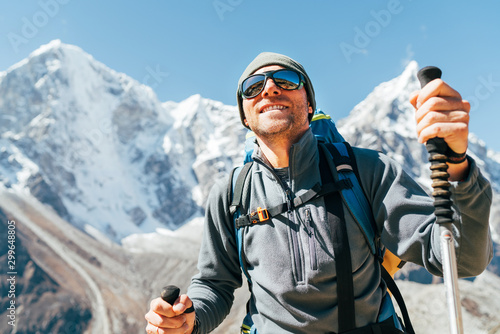 Stampa su Tela Portrait of smiling Hiker man on Taboche 6495m and Cholatse 6440m peaks background with trekking poles, UV protecting sunglasses