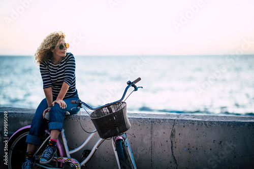 Happy beautiful curly healthy caucasian adult middle age woman sit down on a vintage coloured bike and enjoy the ocean in outdoor leisure activity - trendy people with hapy life
