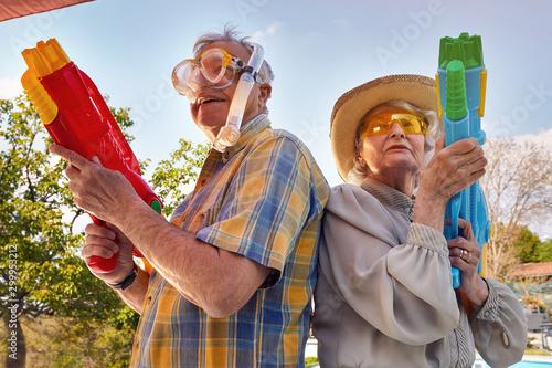 Fotografering Modern Senior couple have fun playing with  water gun.