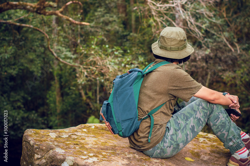 teen girl backpack stay and sitting on nature cliff with forest lanscape background, adventure trip tourism, holiday vacation with travel to moutain