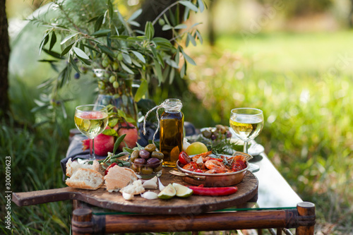 Fotografia Romantic italian lunch outside for a couple: copper pan with delicious and spicy fried shrimps with herbs and garlic, wine, bread, olives