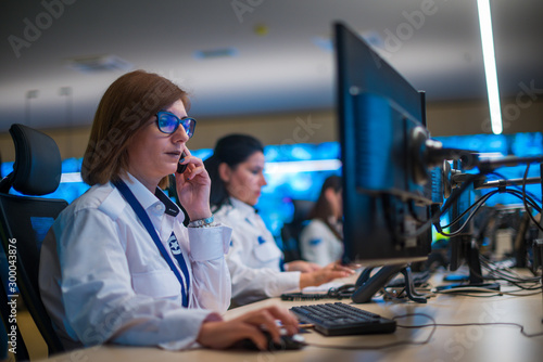 Fotografia Female security guard sitting and monitoring modern CCTV cameras in a surveillance room, talking on a cellphone