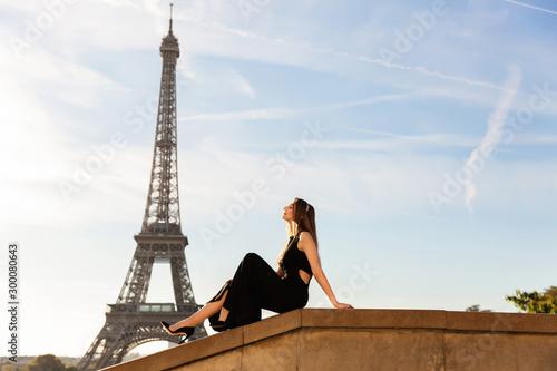 Obraz na plátně Woman in black dress near Eiffel tower. Paris fashion