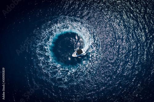 Fotografie, Obraz Boat at sea making a circle birds eye view