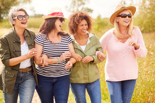 Valokuvatapetti Group Of Mature Female Friends Walking Along Path Through Yurt Campsite