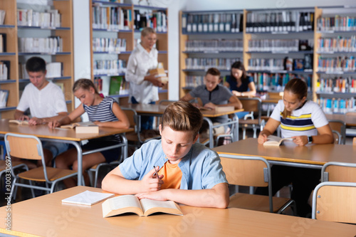 Fotografia Schoolboy preparing for lesson with books in school library indoor
