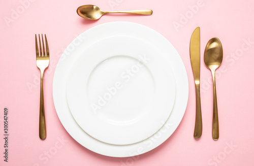 Gold cutlery and dishes set against pink background, formal place setting Fototapeta